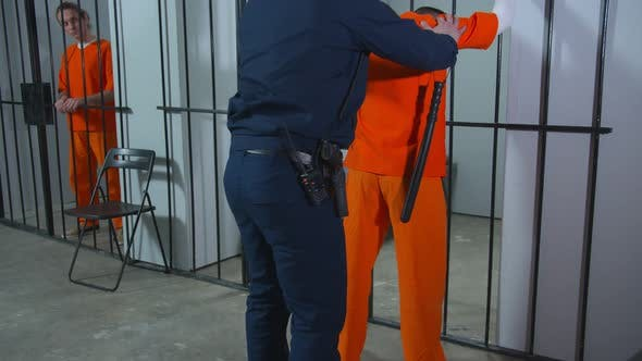 The Jailer Examines the Prisoner. Medium Full Shot