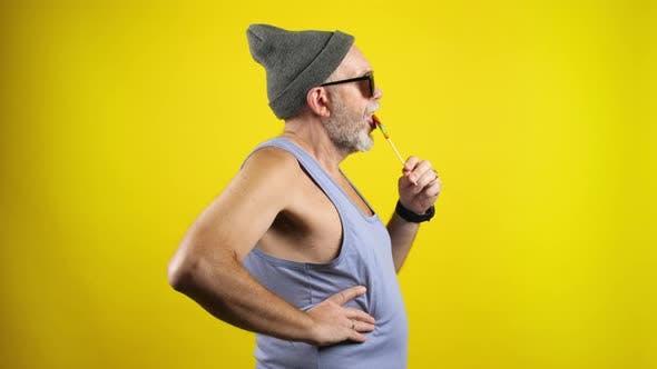 Thumbnail for Trendy bearded senior man licking lollipop