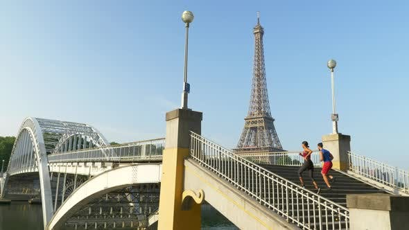 Thumbnail for A couple running across a bridge with the Eiffel Tower.