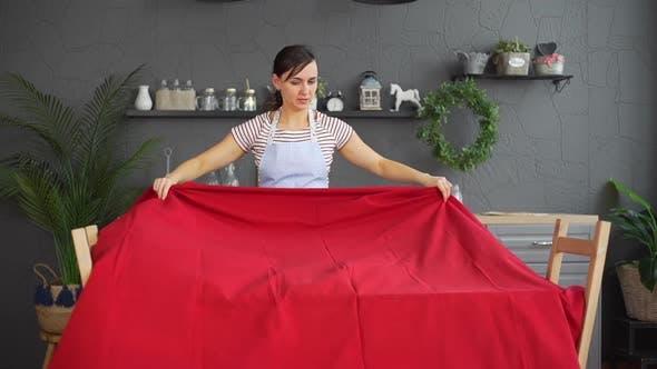 Junge Frau breitet Tischdecke auf einem Tisch