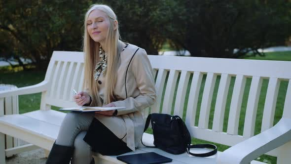 Thumbnail for Woman Sits on the Bench in Autumn Park Makes Notes in a Notebook