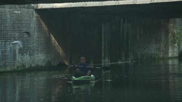 A man on a kayaking adventure in a urban setting