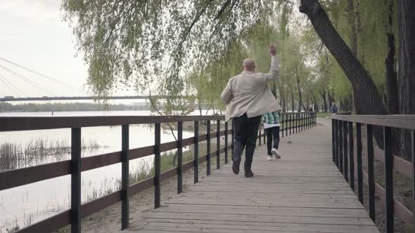 Thumbnail for Little Boy Running Away From His Grandfather on the Wooden Bridge Near the River