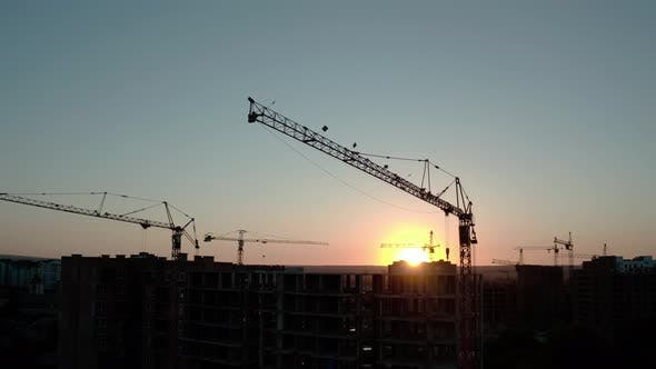 Thumbnail for Aerial Drone View of Silhouette Construction Cranes in Sunset Light. Construction Site Building