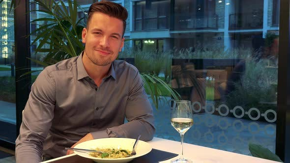 Thumbnail for A Young, Handsome Man Sits at a Table in a Restaurant and Smiles at the Camera
