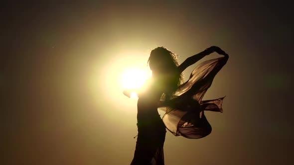 Thumbnail for Girl on the Seashore Gracefully Dances Her Body Against the Sunset. Silhouette. Slow Motion