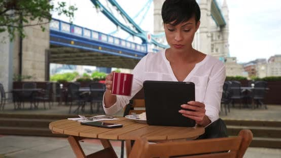 Thumbnail for Mixed race female drinking coffee while using tablet near Tower Bridge in London