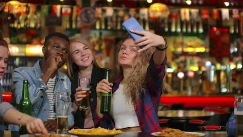 In der Bar oder im Restaurant macht Hispanic Man Selfie von sich selbst und ihren besten Freunden