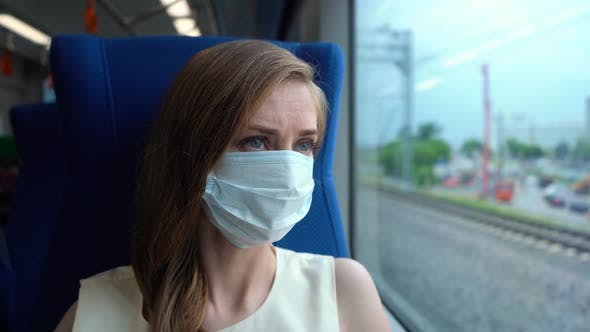 Young Woman in Mask in Moving Train Looking in Window