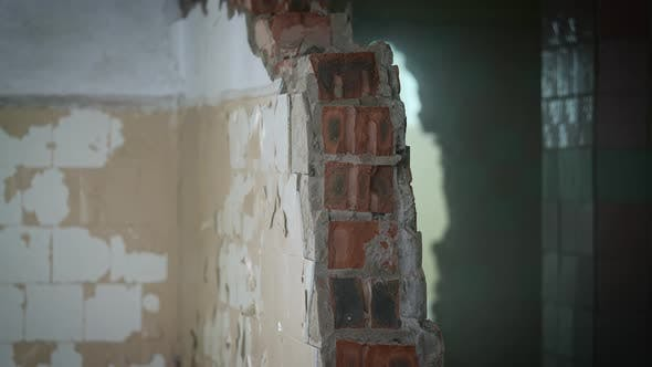 A Worker with a Sledgehammer Demolishes a Brick Wall