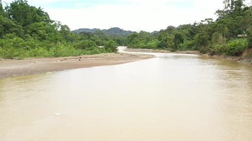 Flying relatively quick directly above a river in a tropical forest