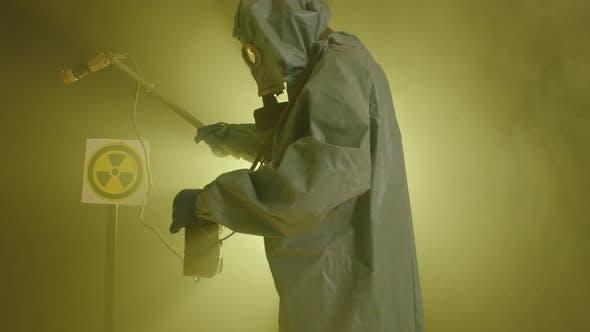 The Concept of Environmental Disaster and Radiation Pollution. A Man in a Radiation Protection Suit