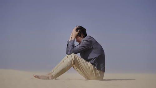 Sad Man is Sitting on a Sand in Desert