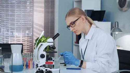 Female Chemistry Professor in Lab Coat Using Pipette To Drop Fertilizers on Something