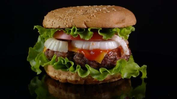 Beef Burger Rotating on a Black Background