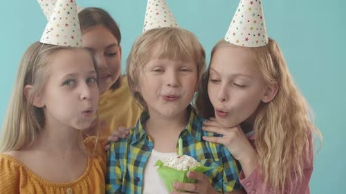 Children Blowing out Candle on Muffin