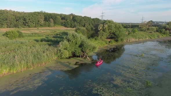 Thumbnail for Drone top view of woman floating in boat on river at sunny summer day.