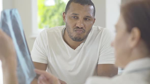 Cover Image for Portrait of Thoughtful African American Man Listening To Blurred Caucasian Woman Explaining Disease
