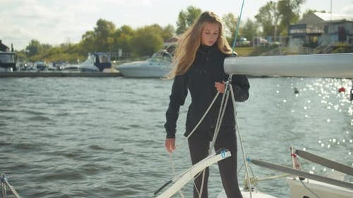 Long-haired Beautiful Girl Stretches a Rope Through a Boom, Prepares for a Sailing Competition on a