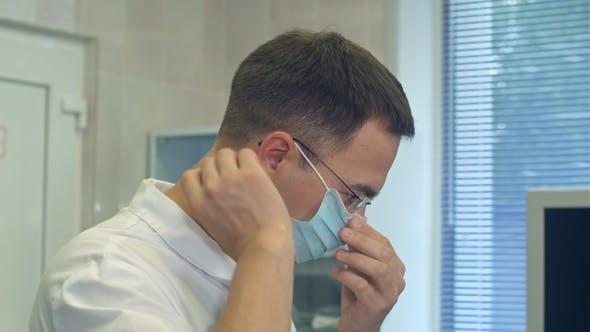 Thumbnail for Junge männliche Arzt setzen chirurgischen Hut auf in einem chirurgischen Raum