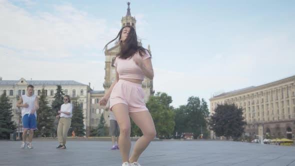Thumbnail for Confident Female Dancer Spinning in Modern Dance on City Square. Portrait of Beautiful Brunette