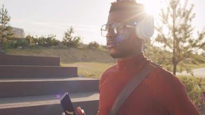 Young Black Man Enjoying Music in Headphones Outdoors