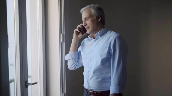 Positive Mid Adult Man Chatting on Phone