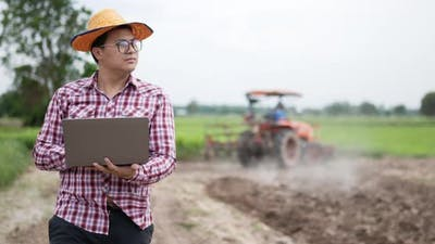 Smart farmer using laptop and walking with tractor