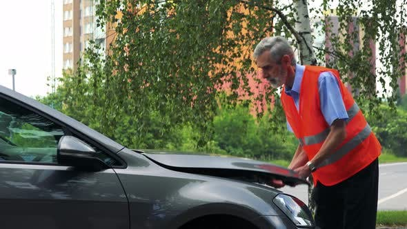Thumbnail for Senior Man Wears Warning Vest, Opens Hood and Controls Engine of the Car