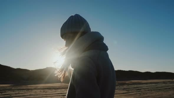 Thumbnail for Cinematic Shot of Beautiful Back Lit Tourist Woman in Winter Clothes Looking at Camera at Windy Sea