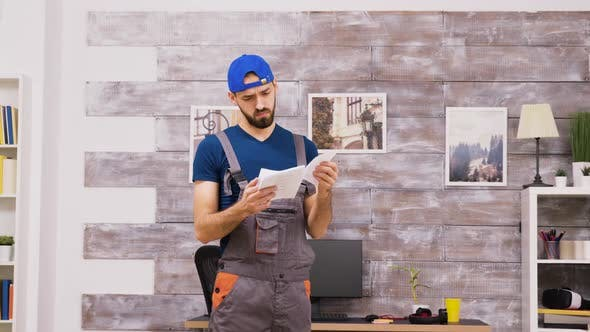 Thumbnail for Male Worker in Coveralls Being Confused While Reading Intructions