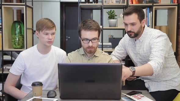 Thumbnail for In the Office, Three Men Work Quietly in Front of One Computer