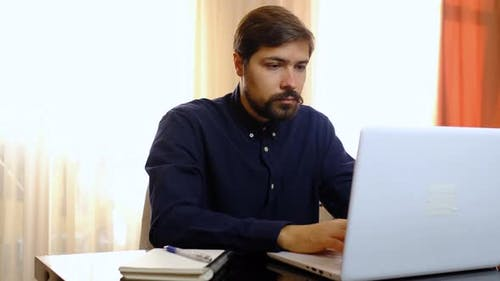 Young Man Freelancer Student Using Laptop Working From Home in Internet