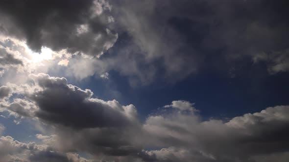 Beautiful 4K time lapse. Sun rays break through white fluffy clouds on vivid blue sky