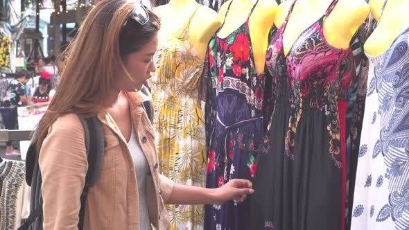 Young Woman Browsing Clothes in the Market