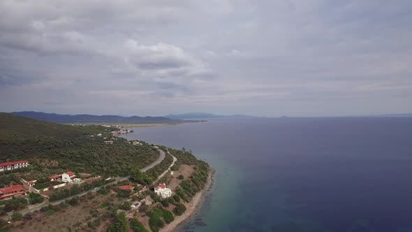 Thumbnail for Aerial Scene of Sea, Coast with Green Hills and Houses Trikorfo Beach, Greece