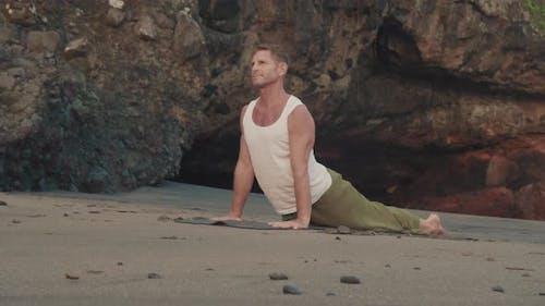 Man Practicing Asanas on Beach