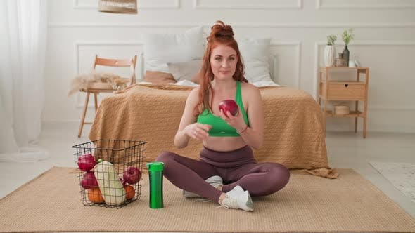 Young Woman in Sportswear Sitting on Floor with Basket of Fruits and Vegetables