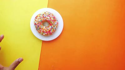 Hand Pick Fresh Colorful Donuts on Color Background