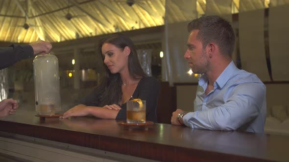 Thumbnail for A man and woman couple having a very cold drink at a bar at a tropical island resort.