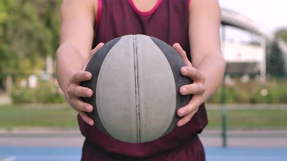 Thumbnail for A Guy Basketball Player Holds a Ball in His Hands and Holds It Out To the Camera. Outdoor Training