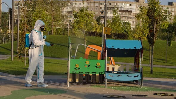 Thumbnail for A Man in a Protective Suit and a Respiratory Gas Mask Disinfects the Slides on the Playground