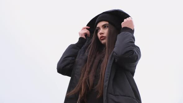 Thumbnail for Fashion Portrait of Trendy Pretty Brunette Girl Putting on a Hood Outdoors. Female Model Wearing