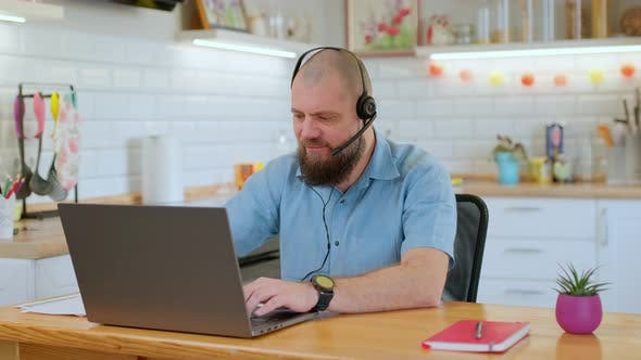 Cheerful Mature Man Emotionally Playing a Game on His Laptop