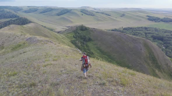 Thumbnail for The Camera Follows a Hiker with a Backpack walking Along the Top of the Hill.