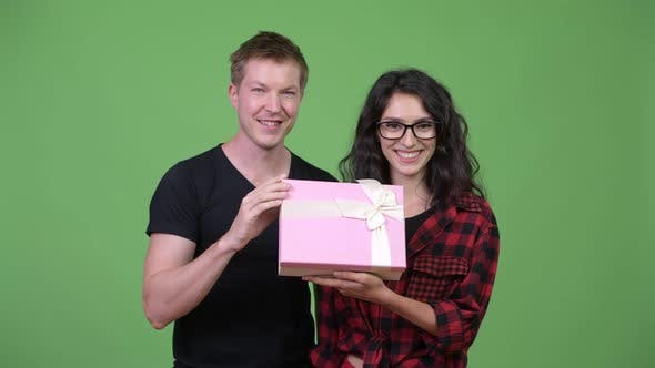 Thumbnail for Young Couple Holding Gift Box Together