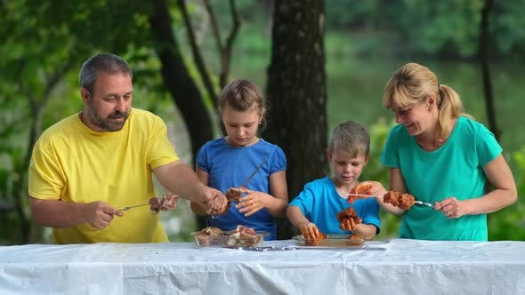 Dad, mom and kids put pickled meat on skewers. Family picnic in the Park