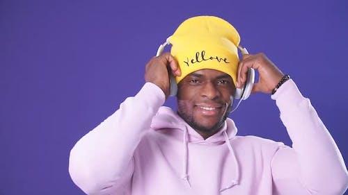 Cute African-American Man in Headphones Dressed in Street Style Wear, Listening To Music