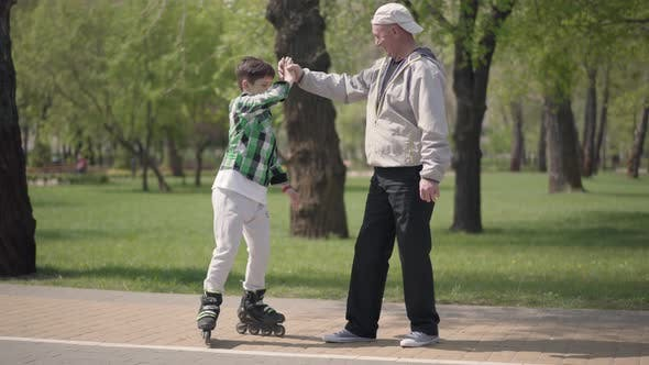 Thumbnail for Adorable Boy in Checkered Shirt Rollerblading in the Park, His Grandfather Catching Him