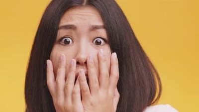 Close Up Portrait of Young Afraid Asian Lady, Feeling Afraid and Panicked , Orange Studio Background